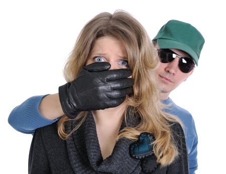 quiet adult: The frightened woman. Man hand covers her mouth. She is shocked and horrified.