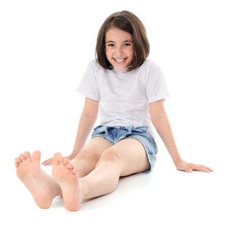 piedi nudi di bambine: Ragazza, sorridente, seduta su un pavimento. Guardando a porte chiuse.