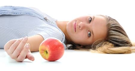The girl and an apple lying on a floor. Looking at camera.   photo