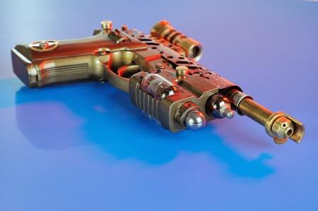Steampunk style future pistol. On a dark blue background Stock Photo - 12385440
