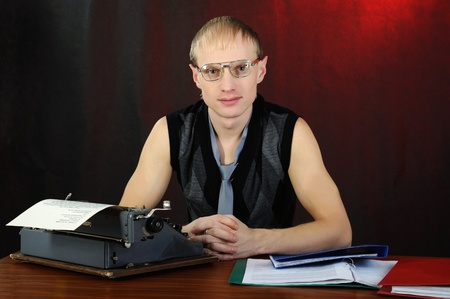Man in eyeglasses with old typewriter. On dark background. photo