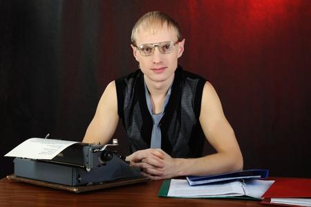 Man in eyeglasses with old typewriter. On dark background. photo