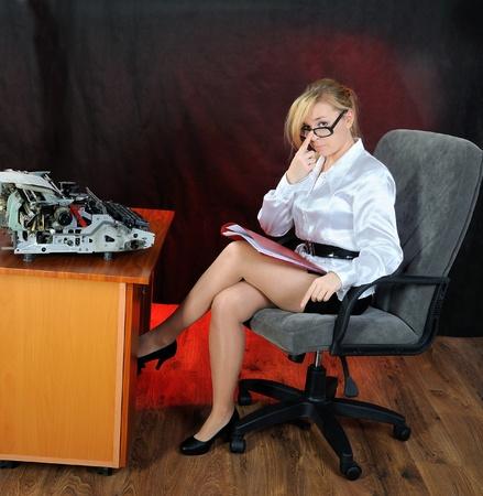 inefficient: Businesswoman in eyeglasses with old typewriter  On dark background  Stock Photo