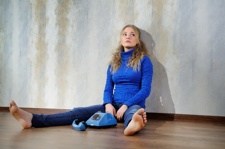 Young woman sitting on a wooden floor with old phone. photo