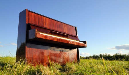 The old wooden piano outdoors. Summer landscape.