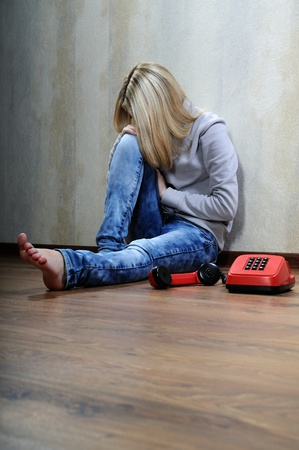 Young woman sitting on a wooden floor with old phone. Stock Photo