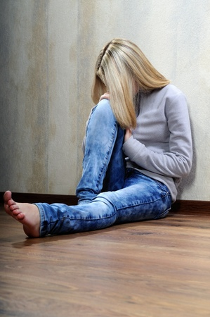 The sad barefooted girl sits on a floor. photo