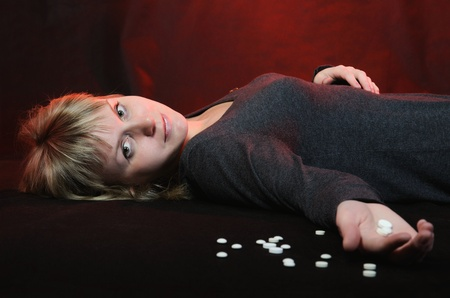 A woman committing suicide with pills. Focus on the face. photo