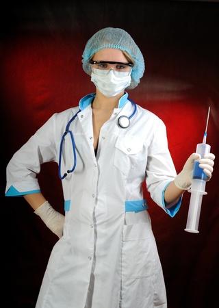 Nurse holding a big syringe. On red background. Stock Photo - 13606837