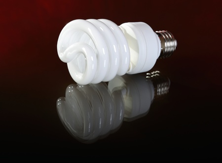 Fluorescent ligth bulb on dark red background photo
