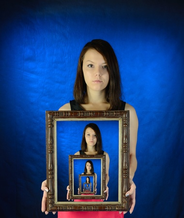 Girl holds the never-ending photo in a frame in her hands.