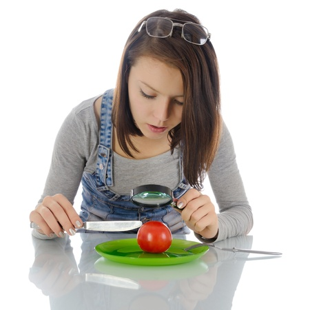 Girl examines a tomato with a magnifying glass, on a white background.