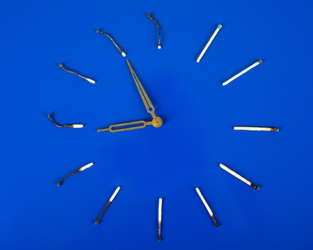 Clock face from burned matches on a dark blue background. photo