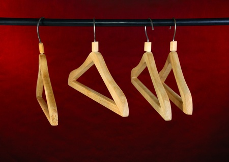 Four empty hangers of wooden. Dark red background. Stock Photo - 15308886