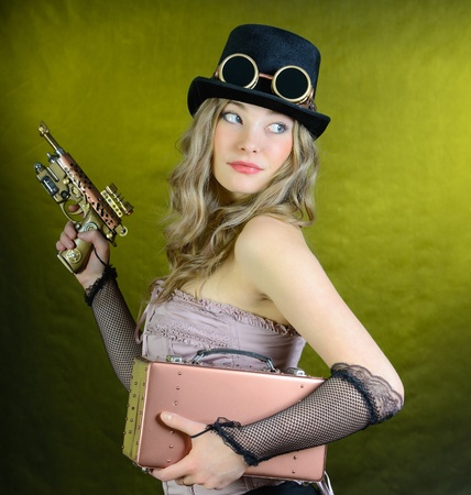 Steampunk girl with pistol and small suitcase to look back photo