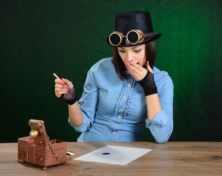 Steam punk girl tries calligraphy. Dark green background. photo