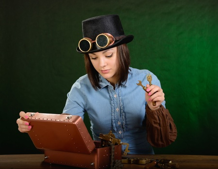 Steam punk girl with tool. Dark green background. photo