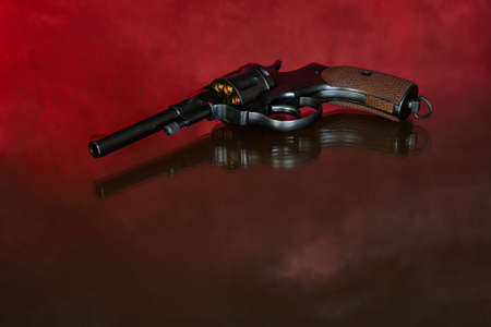Revolver on red background. Vintage pistol revolver.