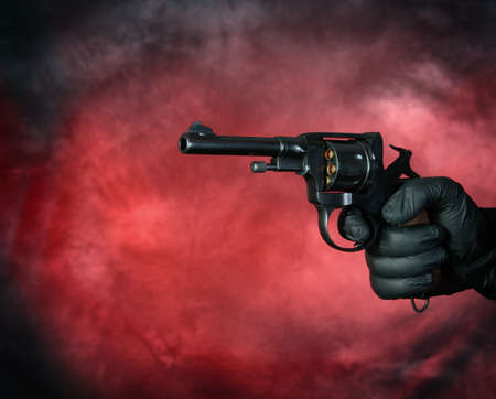 Hand with revolver gun on red background