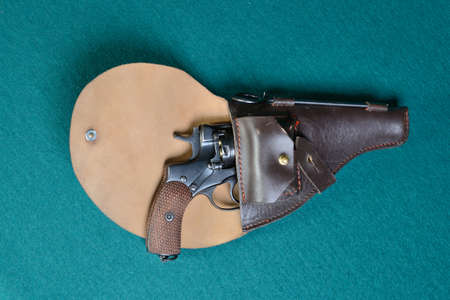 Gun with holster on a on green cloth. Foto de archivo