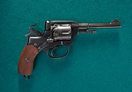 Revolver cocked on green cloth. Vintage pistol revolver.