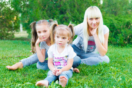 Young mother and two daughters walking in summer park. They are happy. In girls, funny hairstyles. People dressed in jeans and T-shirts. Stock Photo