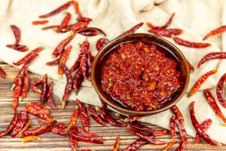 Dried chili on wood grain tabletop and bean paste in porcelain bowl