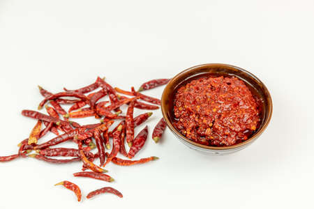 Dried chili on white background and bean paste in porcelain bowl