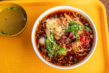 Red soup beef noodles in a big bowl on the table