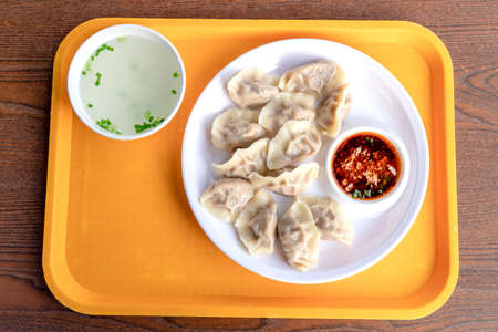 Dumplings and clear soup on a white round plate on the desk