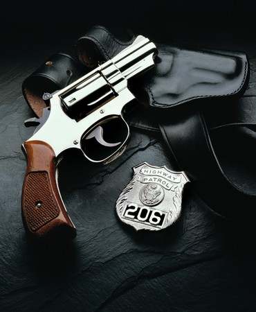 Police gun with holster and badge on dark background