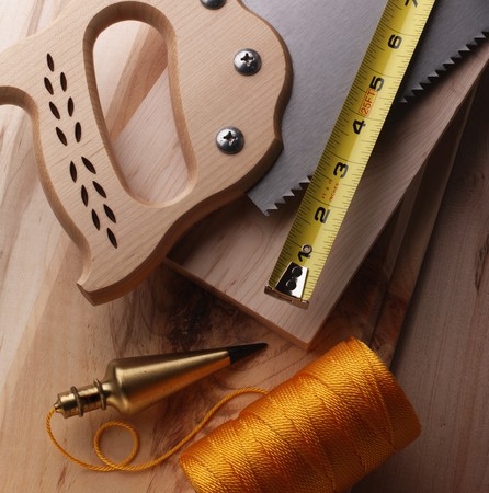 Wood working tools on a wooden background, including saw, ruler and plumb bob Stock Photo