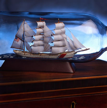 Sailing ship in a glass bottle on antique wooden box