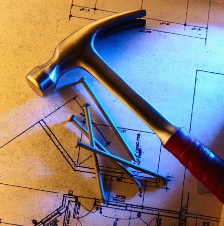 Hammer and nails on blueprints with side light Фото со стока