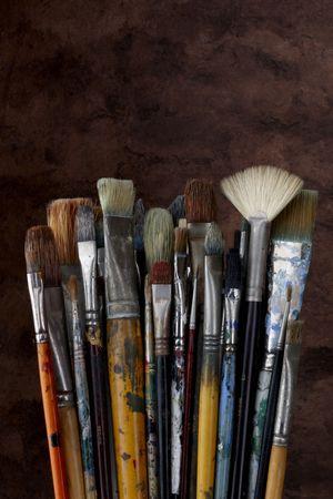 dozens: dozens of artists brushes shot with dark textured background