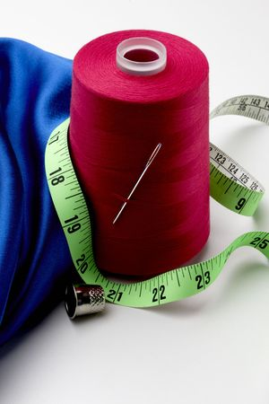 A spool of red thread, blue material, green tape measure, sewing needle and thimble
