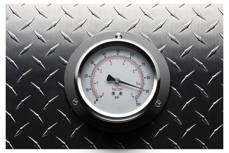 Pressure gauge mounted on textured stainless background