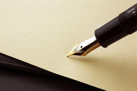 pluma y papel: Pluma estilogr�fica a punto de escribir en papel pergamino