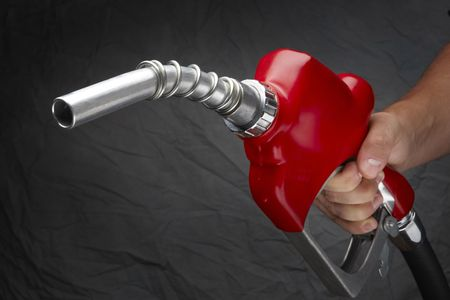 Man with gas nozzle in hand at gas station