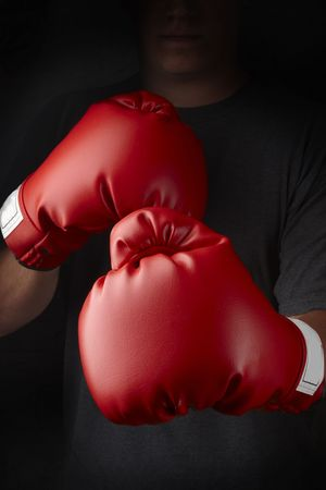 Boxer with red boxing gloves about to throw a punch Stock Photo