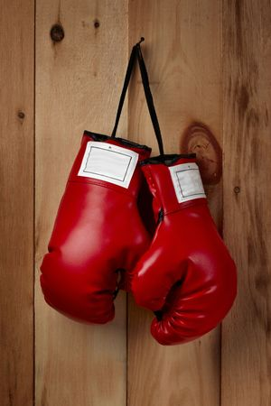 hangs: A pair of red boxing gloves hangs from a nail