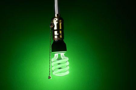 enchufe de luz: color verde que brillan bombilla fluorescente compacta cuelga de un enchufe de la luz