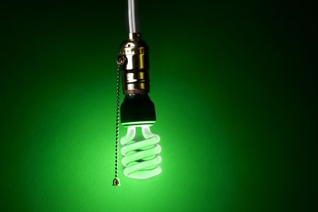 glowing green compact fluorescent bulb hangs from a light socket photo