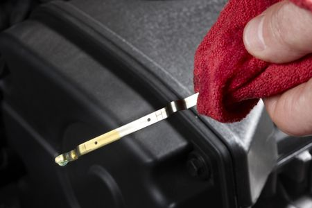 Gas station attendant, holding red rag, checks oil level Stock Photo