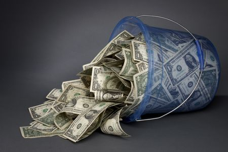 Large blue transparent plastic bucket filled with dollar bills on its side, money spilling out