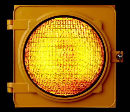 Close up of illuminated amber traffic light lens