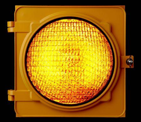 traffic signal: Close up of illuminated amber traffic light lens