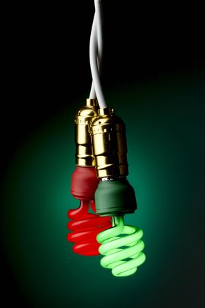 Two lit compact fluorescent bulbs (one green, one red) hanging from sockets 写真素材