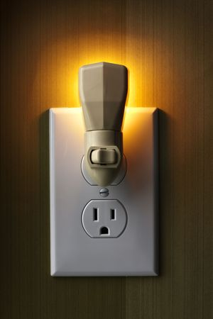 closeup of lit nightlight plugged into wall outlet giving off warm glow