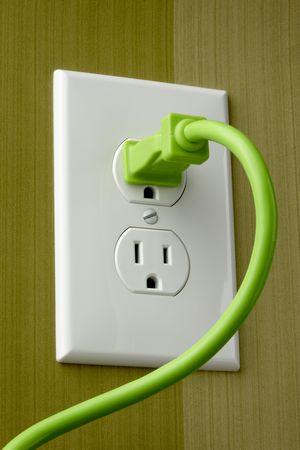 밝은 녹색 전기 코드가 흰색 콘센트에 꽂혀 있습니다. 스톡 콘텐츠